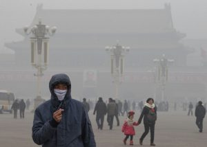 FILE - In this Tuesday, Jan. 29, 2013 file photo, a man wears a mask on Tiananmen Square in thick haze in Beijing. China, one of the most visited countries in the world, has seen sharply fewer tourists this year, with worsening air pollution partly to blame. (AP Photo/Ng Han Guan, File)